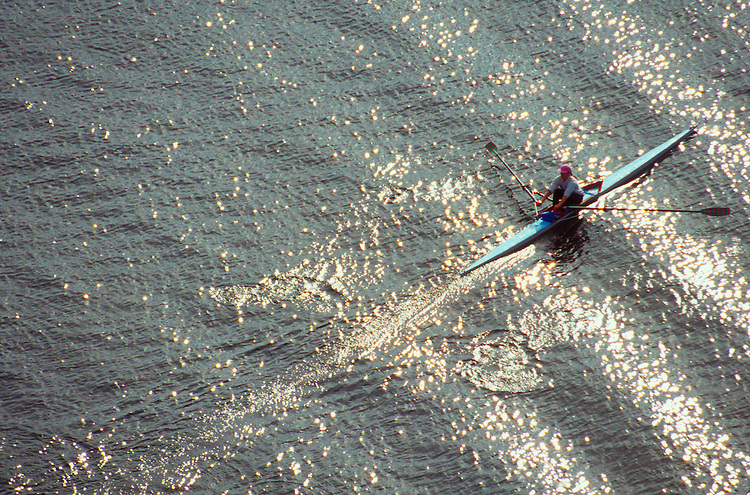 Rowing, Looking down on a model released woman rower rowing a single racing shell through a set of waves..