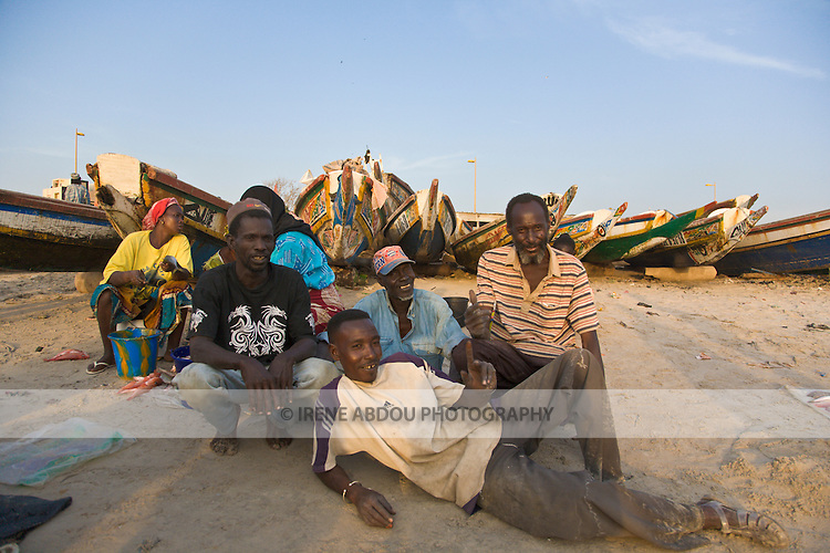 A group of men pose for a photo in front of the colorfully painted fishing boats that line the beach at this fish market in Dakar, Senegal.