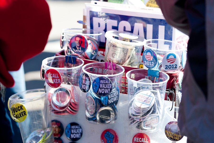 Political buttons are pictured for sale as more than 60,000 citizens, public workers, teachers and union members gathered during a Reclaim Wisconsin protest rally held outside the Wisconsin State Capitol in Madison, Wis., on March 10, 2012. One year earlier, Wisconsin's Republican-controlled legislature pushed through Gov. Scott Walker's bill to strip unions and public workers of many collective bargaining rights. (Photo by Jeff Miller for SEIU)