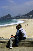 Rio de Janeiro, Brazil. Fully dressed couple sitting on a parapet wall drinking a coconut looking down Copacabana Beach.