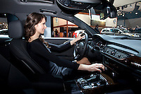 A woman inspect an Audi at the 2013 New York International Auto Show in New York March 27, 2013. The 113th New York International Auto Show, which runs from March 29 to April 7, features 1,000 vehicles as well the latest in tech, safety and innovation. Photo by Eduardo Munoz Alvarez / VIEWpress.