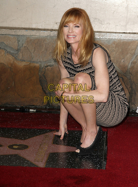 Marg Helgenberger.Marg Helgenberger Walk of fame star ceremony in the Category of Television Held On Hollywood Blvd., Hollywood, California, USA..January 23rd, 2012.full length print pattern striped stripes brown beige black dress sleeveless crouching .CAP/ADM/KB.©Kevan Brooks/AdMedia/Capital Pictures.