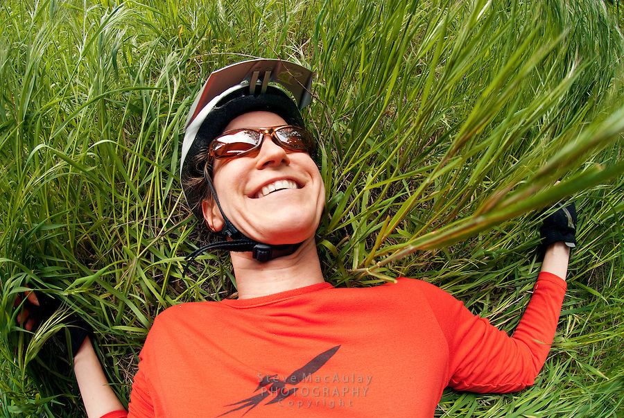Smiling female mountain biker close-up as she lays in tall grass.