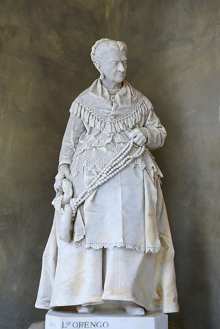 "Picture and image of the stone sculptured  funeral monument of Caterina Campodonico, also called ""The Peanuts Seller"" carrying a string of peanuts and donuts that she sold on the streets of Genoa. Completed while she was still alve by sculptor Lorenzo Orengo, who was the most important artist of the Bourgeois Realism, greatly sought after by the member of the middle class. The Staglieno Monumental Cemetery, Genoa, Italy"