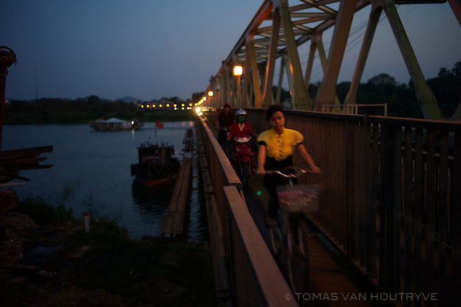 A girl rides her bike across the Da Vien bridge in Hue, Vietnam on 25 February 2010.