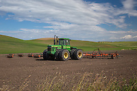 A tractor in a field in the Palouse. The Palouse Is a region of where there are no continuous valleys, and the hills do not connect to make long ridges. These hills were not created by rivers and streams, as is most of our landscape, but formed more like sandunes, with winds depositing silt to form of some of the most fertile soil in the country.