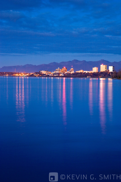 Photo of the Anchorage City Skyline reflected in the waters of Knik arm after sunset, high tide, taken from the Tony Knowles Coastal Trail, fall, Southcentral Alaska, USA.