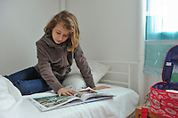 Girl (9) reading comics on her bed, in bedroom (Licence this image exclusively with Getty: http://www.gettyimages.com/detail/97538626 )