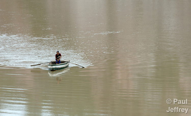 A young man maneuvers a boat on the river at Iboca in the Chaco region of Bolivia.