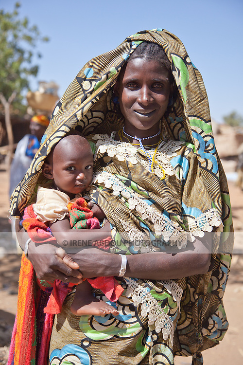 Fulani woman and child at the village market of Bourro in northern Burkina Faso.  The Fulani are traditionally nomadic pastoralists, crisscrossing the Sahel season after season in search of fresh water and green pastures for their cattle and other livestock.