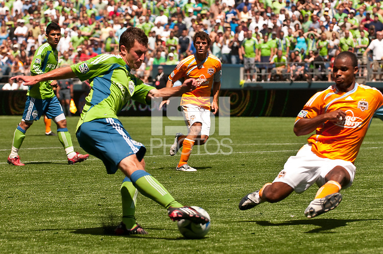 Stephen King (l) of the Seattle Sounders dekes around Ricardo Clark (r) of the Houston Dynamos in the match at the XBox Pitch at Quest Field on July 11, 2009. The Sounders defeated the Dynamo 2-1.