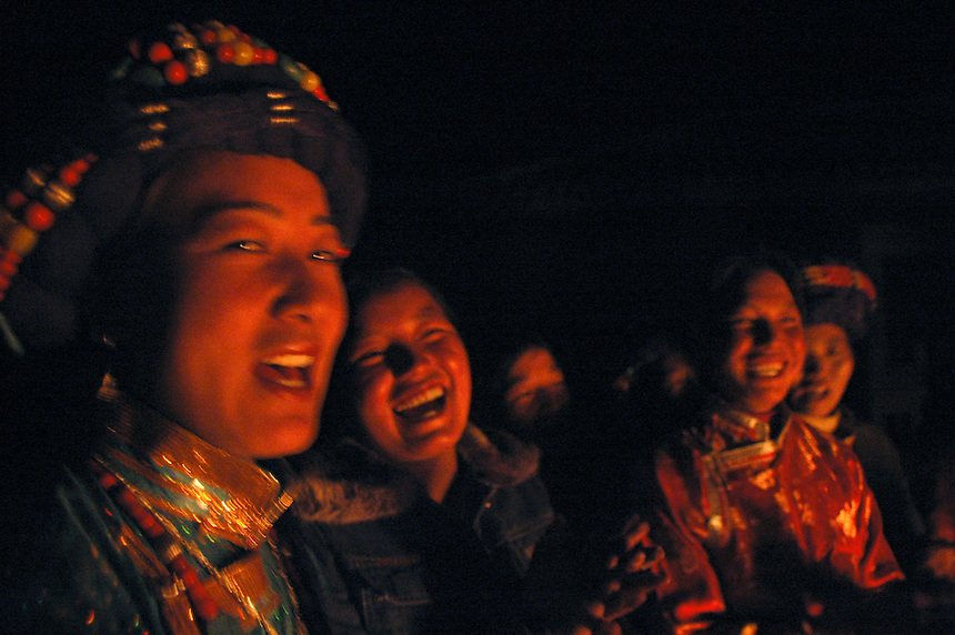Ata Latsu, left, joins a singing chorus of women as they exchange impromptu bantering in song with a group of Moso men. The songs follow a set tune, but the singers must quickly create lyrics in a competition of wit between the sexes.