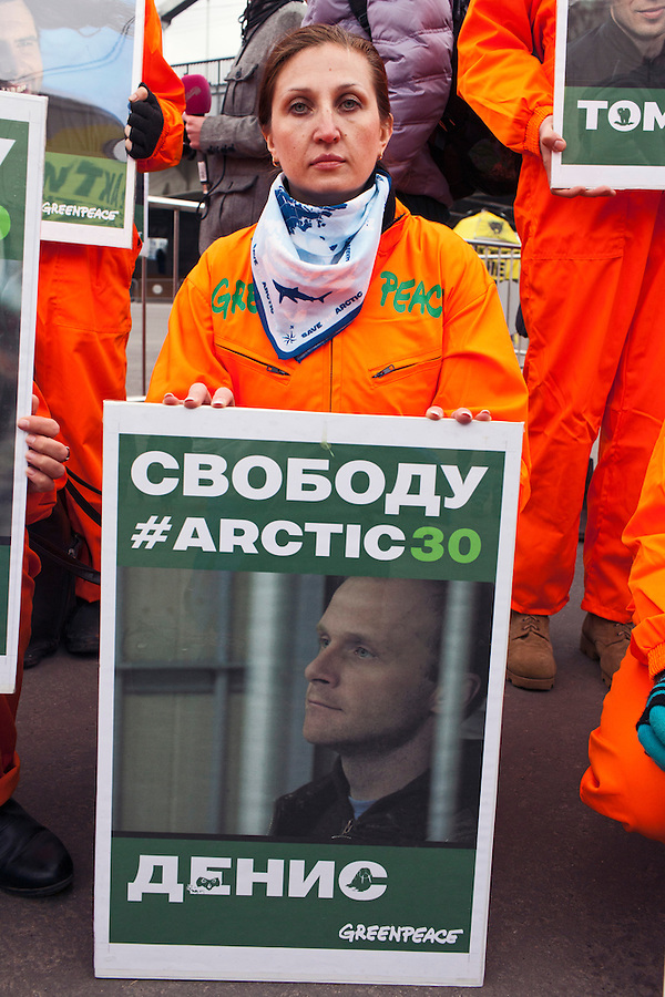 Moscow, Russia, 05/10/2013.<br /> A Greenpeace activist holds a portrait of Russian photojournalist Denis Sinyakov behind bars in Murmansk court at a demonstration in support of the crew members of the ship &quot;Arctic Sunrise&quot; . The entire crew and accompanying journalists including Sinyakov have been charged with piracy after being seized at gunpoint by Russian coastguards while protesting at a Gazprom off-shore drilling platform In the Arctic.