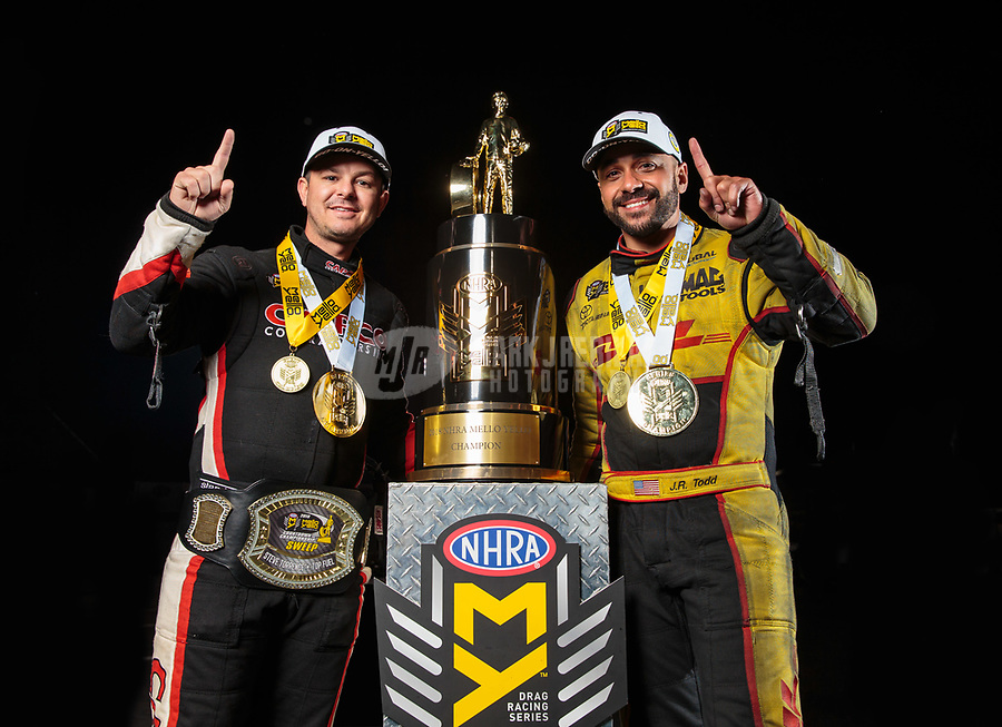Nov 11, 2018; Pomona, CA, USA; NHRA top fuel driver Steve Torrence (left) and funny car driver J.R. Todd pose for a portrait as they celebrate after winning the Auto Club Finals and the world championships at Auto Club Raceway. Mandatory Credit: Mark J. Rebilas-USA TODAY Sports