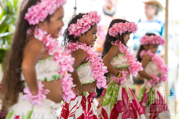 Girls wearing pink plumeria lei and haku head lei perform a hula in Hale'iwa, North Shore, O'ahu.