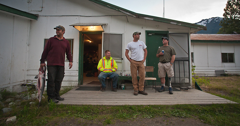 Part of the Wakhash Contracting crew enjoys some R&R  including rich salmon fishing in the inlet  at the end of a long (10 hours or more) and hot summer's day of work. From left to right: South African import Jason Davison with salmon (driller/blaster), Randy Sumner (loader operator), Dyson Parkin (loader operator), Mike Davis (loader operator). The Wakhash crew is younger than many I've photographed in recent years.