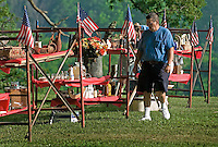 A man walks among items for sale  at a rural yard sale on a farm near West Liberty, Ohio.<br />