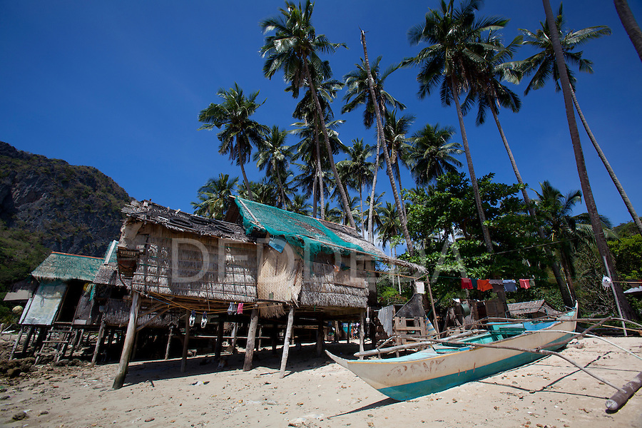 Palm-leaf stilt houses on the beach in the village of Corong Corong, near El Nido, the gateway to the Bacuit Archipelago in Palawan, Philippines.