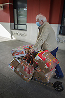 Switzerland. Canton Ticino. Lugano. Railway Station. An elderly man wears a mask on his face to protect himself from the Coronavirus (also called Covid-19). The man pushes a push scooter heavy loaded with fully loaded Migros shopping bags. Migros is Switzerland's largest retail company and its largest supermarket chain. It is structured in the form of a cooperative society (the Federation of Migros Cooperatives), with more than two million members. 10.03.2020 © 2020 Didier Ruef