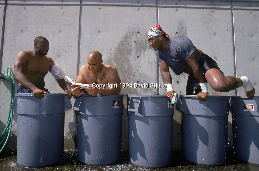 Chicago Bears defensive lineman Chris Zorich, center, reads a book as he cools off in an ice bath after an NFL football practice during training camp on July 1, 1994 at University of Wisconsin in Platteville,Wisconsin. (Photo by David Stluka)