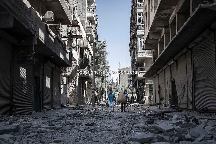 Syrian civilians walk through the debris of smashed buidings as they carry up their belongings while moving away from their home at the frontline in Bustan Al-Bashar/Al-Midan battlefield in Aleppo City.