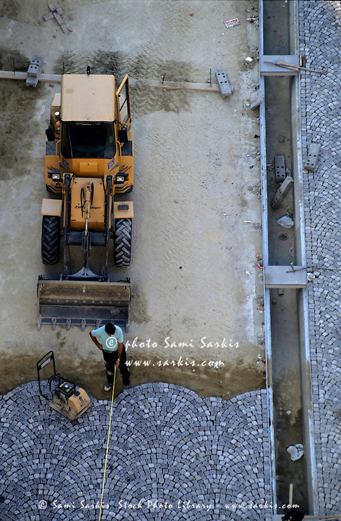 Man working laying cobblestones on a city street, Paris, France.