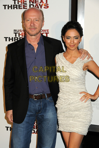 "PAUL HAGGIS & NAZANIN BONIADI .""The Next Three Days"" Los Angeles Screening held at the Directors Guild of America, West Hollywood, California, USA, 16th November 2010..half length hands on hips sleeveless white ruched mono dress blue purple shirt black jacket jeans  .CAP/ADM/BP.©Byron Purvis/AdMedia/Capital Pictures."