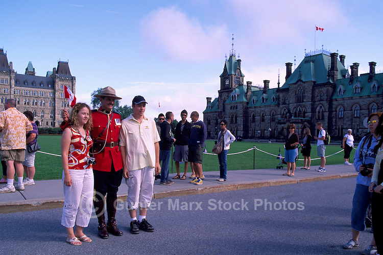 Parliament Buildings on Parliament Hill, in the City of Ottawa, Ontario, Canada - Tourists posing with RCMP Officer in front of Centre Block (built 1865 - 1927) and East Block (built 1867 and 1910)
