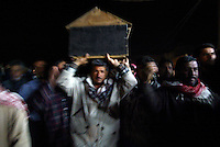 Baghdad, Iraq, March 28, 2003.Men carry the body of one of the 52 victims of the unidentified missile that exploded at dusk in the middle of a crowded market in Al Shuala', a very poor area of North West Baghdad.