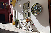 A bicycle leans against a shop wall in Seville, Spain