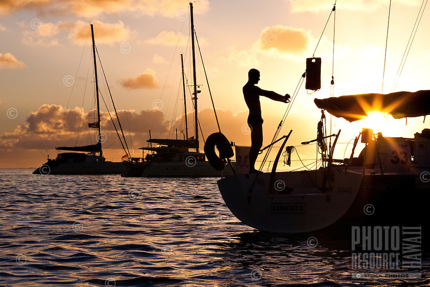 Man stretching on yacht at sunrise in lagoon off Tahaa Island