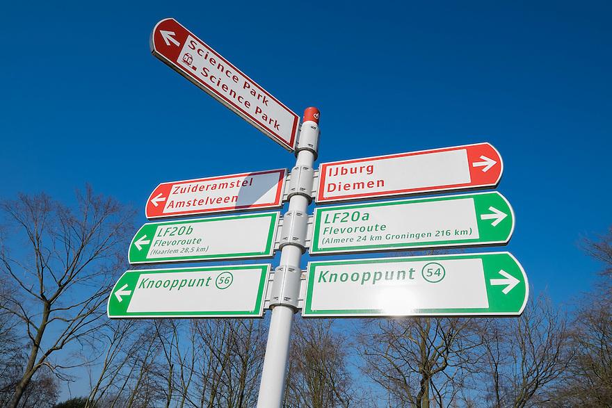 Nederland, Amsterdam, 13 feb 2015<br /> Richtingaanwijzers voor fietsers op een fietsroute in Amsterdam Oost die vlak langs Amsterdam Science Park loopt. <br /> Foto: (c) Michiel Wijnbergh