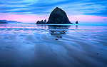 Oregon, North coast, Cannon Beach. Water retained in ripples in the sand reflect the morning sky and Haystack Rock.