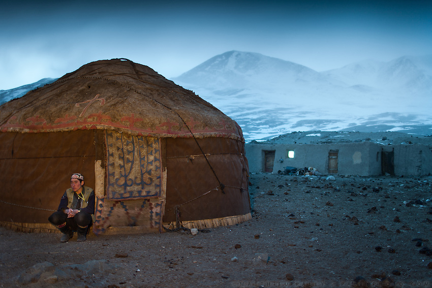A young Kyrgyz shepherd squats in front of his yurt..The Kyrgyz settlement of Tchelab, near Chaqmaqtin lake, Haji Bootoo Boi's camp...Trekking through the high altitude plateau of the Little Pamir mountains, where the Afghan Kyrgyz community live all year, on the borders of China, Tajikistan and Pakistan.