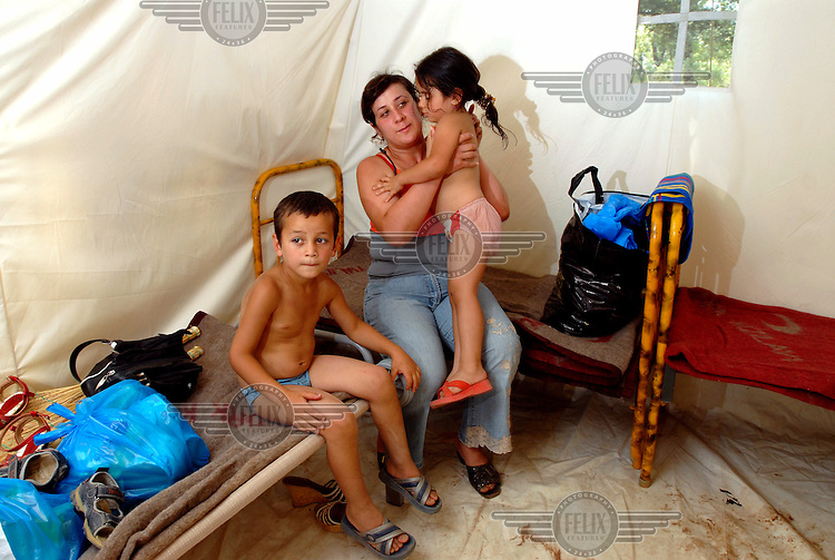 Lela Gvinadze and her two young children, six year old Dato and three year old Nino, sit together in their temporary accomodation at a tented IDP (Internslly Displaced Persons) camp in the Southeast of the country.