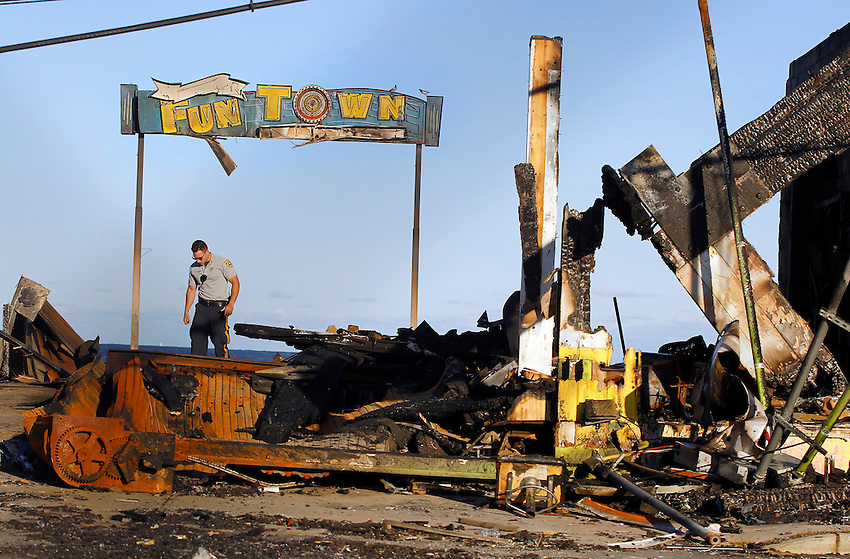 SEASIDE PARK, NJ (Sept. 17, 2013) — Seaside Park police officer John Rossetti walks off the ruined boardwalk where the Funtown Pier burned earlier in the week, hours after Ocean County Prosecutor Joseph D. Coronato the fire investigation task force has ruled the catastrophic fire here accidental — a result of inaccessible electrical wiring beneath the boardwalk that was corroded by saltwater during the Sandy storm surge.