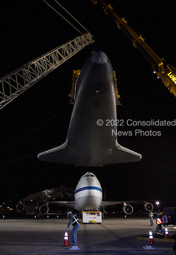 Space shuttle Enterprise is held aloft by a yellow sling and a set of cranes after it was removed from the top of NASA's 747 Shuttle Carrier Aircraft early Sunday morning at John F. Kennedy (JFK) International Airport in New York, Sunday, May 13, 2012 .The 747 was towed backwards so that Enterprise could be lowered. The shuttle will be placed on a barge that will move by tugboat up the Hudson River to the Intrepid Sea, Air & Space Museum in June. The shuttle will be lifted by crane and placed on the flight deck of the Intrepid, where it will be on exhibit to the public starting this summer in a temporary climate-controlled pavilion.  .Mandatory Credit: Kim Shiflet / NASA via CNP