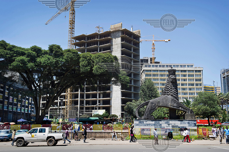 Construction of new apartment buildings taking place around a statue of an Abyssinian lion.