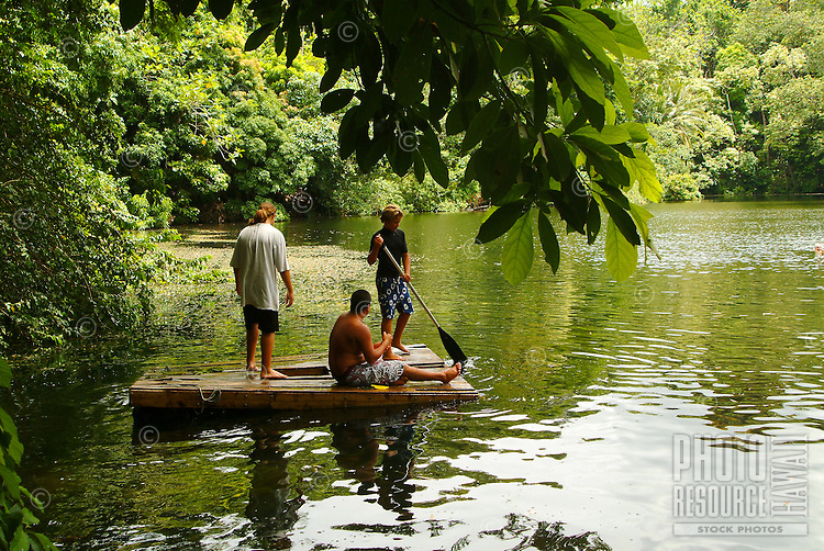 Three boys on a raft at green lake, a special lush area in the Kapoho area of the Big island