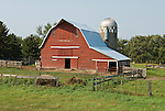 Red wooden barn with gambrel roof, silo, North Dakota.