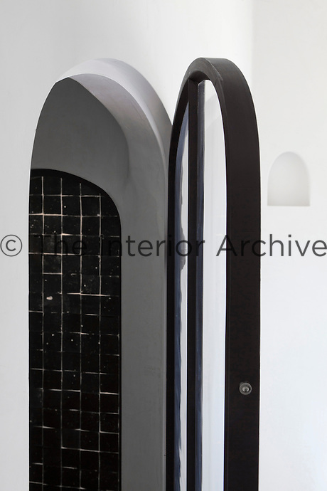 An arched metal and glass door opens into the tiled shower room