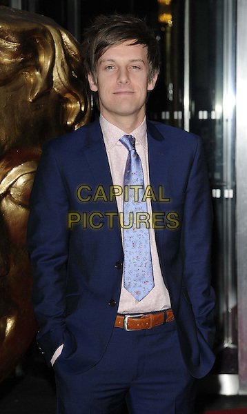 Chris Ramsey.attended the British Academy ( BAFTA ) Video Game Awards, London Hilton Park Lane Hotel, London, England..March 5th, 2013.half length blue suit pink shirt pattern print  hands in pockets.CAP/CAN.©Can Nguyen/Capital Pictures.
