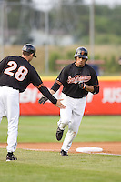 July 7, 2009: Salem-Keizer Volcanoes' Juan Martinez gets some love from third base coach Derin McMains after hitting a home run during a Northwest League game against the Tri-City Dust Devils at Volcanoes Stadium in Salem, Oregon.