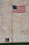 Washington DC, American flag flying at the base of the Washington Monument above two women in the lee of the wind, USA