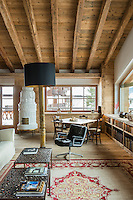 A vintage Eames Lobby chair  sits under a huge standard lamp on a Josephine and Herekè carpet in the living room of Cà dei Frassini in Cortina d'Ampezzo