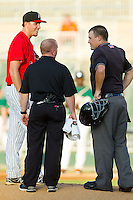 Kannapolis Intimidators starting pitcher Kyle Hansen (51) smiles as home plate umpire Cody Oakes and trainer Cory Barton check on him after he was hit in the buttocks by a line drive during the South Atlantic League game against the Greensboro Grasshoppers at CMC-Northeast Stadium on July 15, 2013 in Kannapolis, North Carolina.  The Intimidators defeated the Grasshoppers 4-0.   (Brian Westerholt/Four Seam Images)