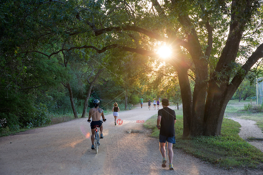 Summer day finds local runners and bicyclist exercise to stay fit outside on the Lady Bird Lake Hike and Bike Trail as part of a healthy lifestyle in downtown Austin, Texas - stock image.