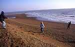 AWY796 Family playing skipping game with rope found on beach Shingle Street Suffolk England