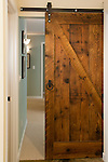A sliding pocket door, made from reclaimed barn wood, separates the family room from the mudroom in this newly remodeled basement.