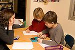 Education elementary Grade 3 science classroom female teacher explaining experiment method to two male students  horizontal